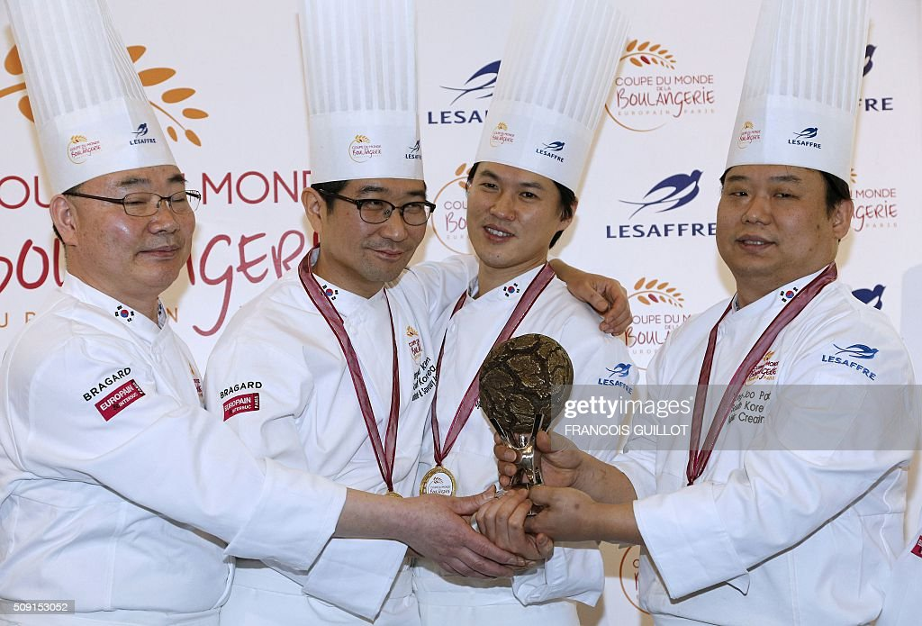 South Korea's team celebrate with their trophy after winning the first place during the Bakery world cup, as part of the Europain fair, on February 9, 2016, in Villepinte near Paris. / AFP / FRANCOIS GUILLOT