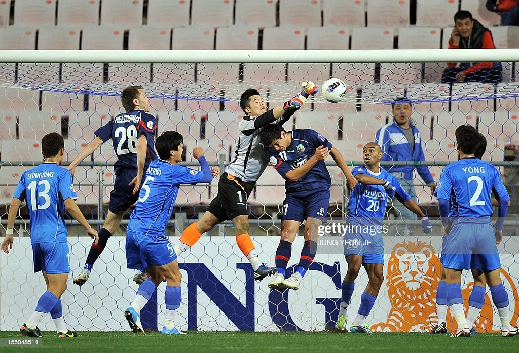 South Korea's Ulsan Hyundai goalkeeper Kim Young-Kwang (C) punches the ball against Uzbekistan's Bunyodkor forward Murzoev Kamoliddin (3rd R) during the AFC Champions League semi final match in Ulsan, about 300 kms southeast of Seoul, on October 31, 2012. South Korea's Ulsan Hyundai reached their first ever AFC Champions League final after they weathered an early onslaught to beat Bunyodkor 2-0 for a 5-1 aggregate win. AFP PHOTO / JUNG YEON-JE