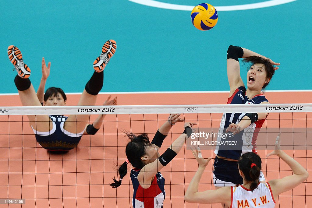 South Korea's Yang Hyo-Jin (R, top) spikes as China's Ma Yunwen (R) attempts to block during the Women's preliminary pool B volleyball match between China and South Korea in the 2012 London Olympic Games in London on August 5, 2012.