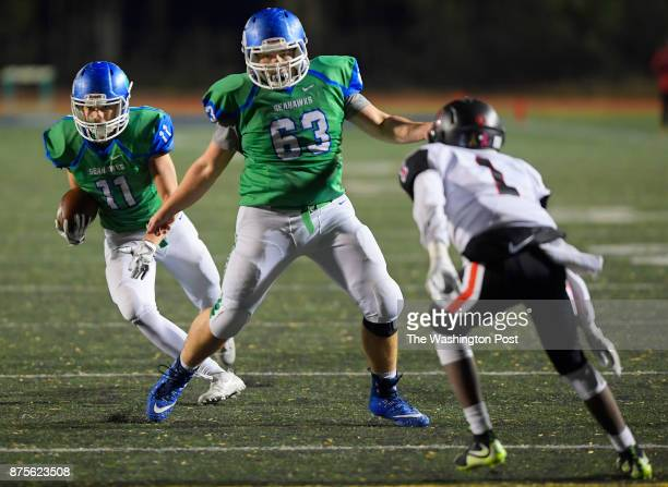 South Lakes' Noah Seneca left runs behind the blocking of offensive lineman Jacob McCarty center as Madison's Alex Jalloh closes in during South...
