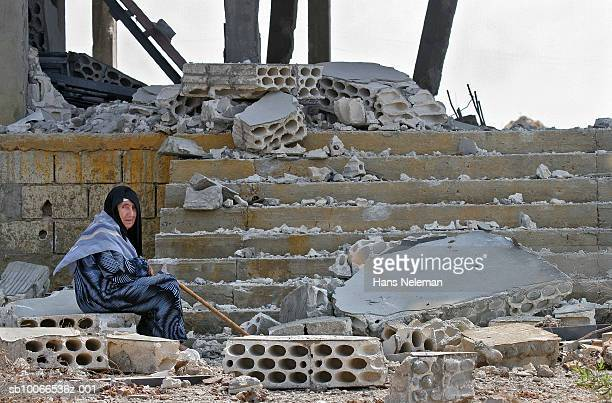 South of  Lebanon, Senior woman sitting in front of destroyed house
