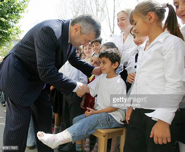 South Ossetian President Eduard Kokoity greets a boy with a broken leg during 'first bell' activities in Tskhinvali on September 1 the traditional...