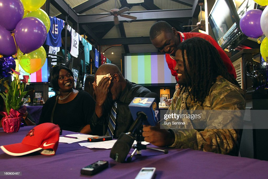 South Plantation Running Back Alex Collins sits down with his Aunt Loretta Collins, his father Johnny Collins to sign with the University of Arkansas on Thursday, February 7, 2013, in Plantation, Florida. Collins' birth father, Johnny, signed his national letter-of-intent during a ceremony at Kim Bokamper's Sports Bar and Grill. The five-star recruit's signing had been delayed because his mother, Andrea McDonald, had refused to sign his national letter-of-intent.