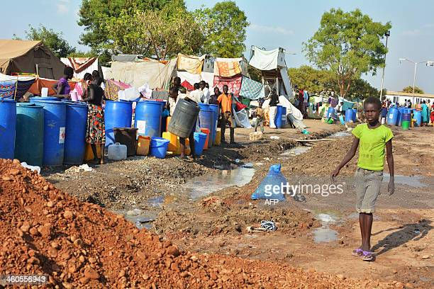 A South Sudanese child walks next to a queue of IDP's as they wait for water rations at an encampment within the United Nations Mission in South...