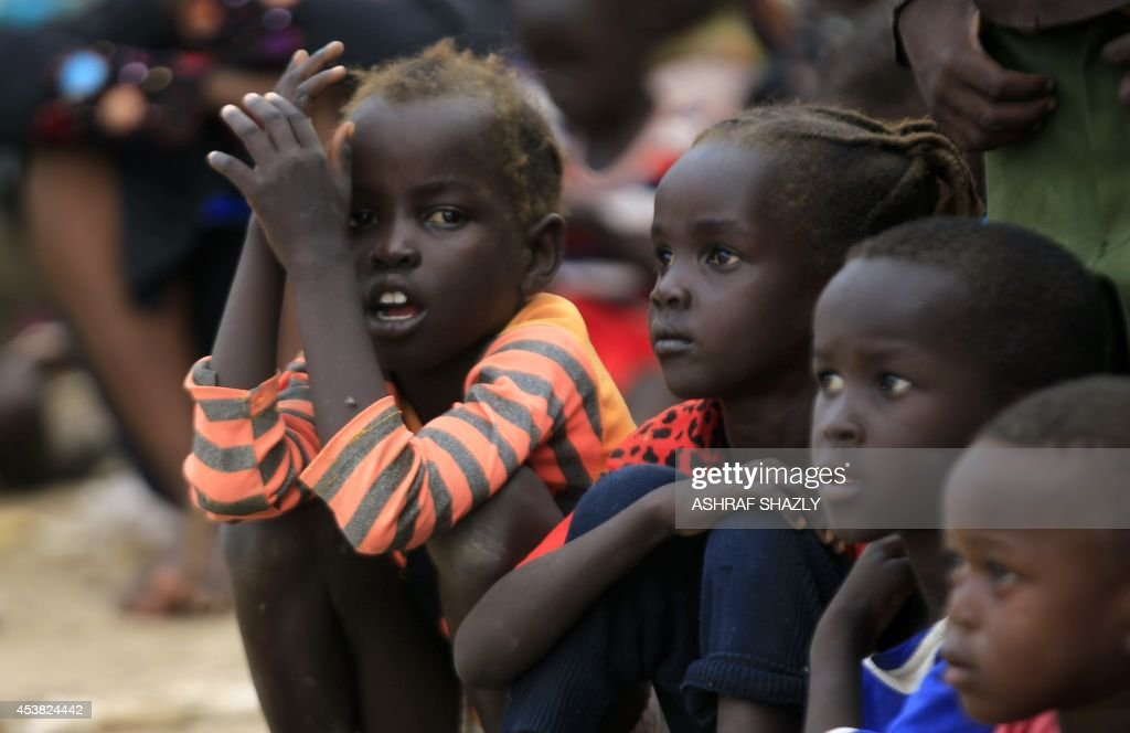 South Sudanese children sit watching the Melody Dance Group as they perform marking World Humanitarian Day in the grounds of the Andalos camp some 30...