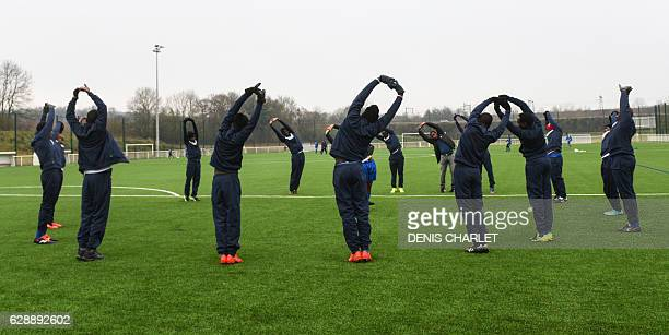 CORRECTION South Sudanese migrants stretch prior to a friendly football match between migrants and the local amateur team in the Croisilles reception...