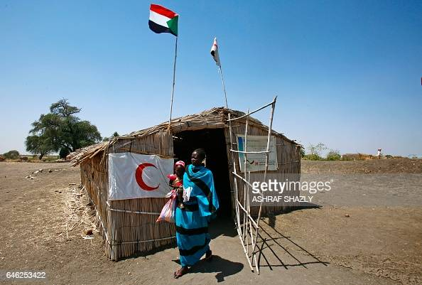 A South Sudanese refugee and her children leave a Red Crescent tent as they flee across the border in Sudan's White Nile state on February 28 2017...
