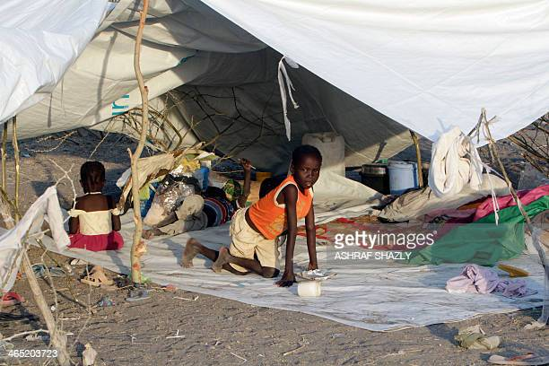 A South Sudanese refugee child looks on under a makeshift tent at a camp run by Sudanese Red Crescent where he arrived with his family after fleeing...