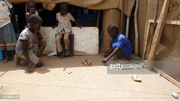 South Sudanese refugee children play with batteries outside a makeshift hut at the Dar es Salaam refugee camp in the capital Khartoum on June 28 2012...