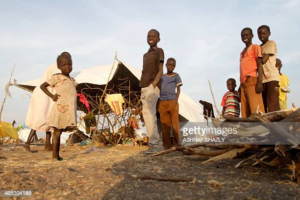 South Sudanese refugee children pose in front of a makeshift tent at a camp run by Sudanese Red Crescent where they arrived after fleeing battles...