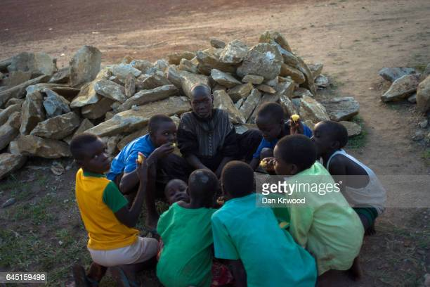 South Sudanese refugee families share out food served at one of the World Food Programme's hot meals points on February 24 2017 in Kuluba Uganda The...