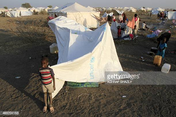 South Sudanese refugee stand near makeshift tents at a camp run by Sudanese Red Crescent where they arrived after fleeing battles between rebel and...