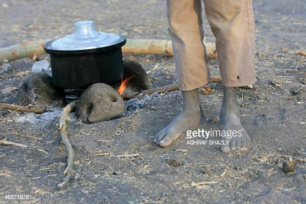 A South Sudanese refugee stands as he prepares food at a camp run by the Sudanese Red Crescent on January 26 2014 in the western part of Sudan's...