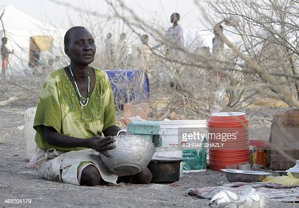 A South Sudanese refugee woman sits near kitchen ustensils at a camp run by Sudanese Red Crescent where she arrived after fleeing battles between...