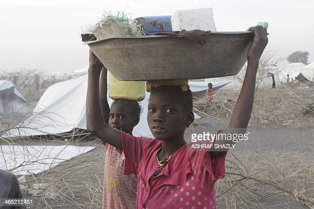 South Sudanese refugees carry belongings outside makeshift tents at a camp run by the Sudanese Red Crescent on January 26 2014 in the western part of...