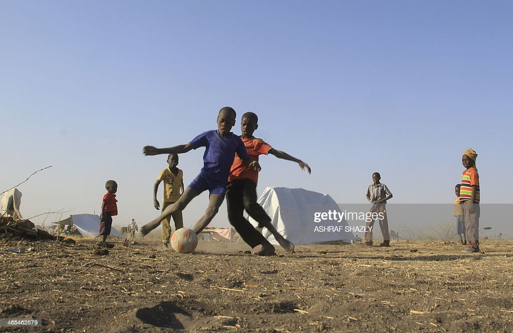 South Sudanese refugees play football at a camp run by the Sudanese Red Crescent on January 27, 2014 in the western part of Sudan's White Nile state, about 30 kilometres from South Sudan, after fleeing battles between rebel and government forces. Kuwait's Red Crescent, the United Nations, and Sudan's aid commission have provided the camp with assistance including shelter and food, a representative of the Red Crescent said, putting the camp population at about 8,000.