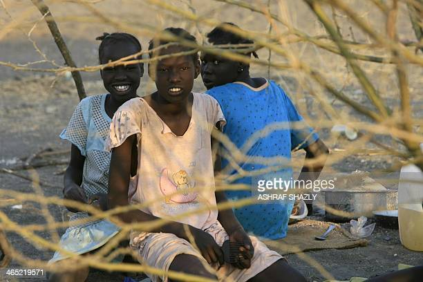 South Sudanese refugees sit in the shade of a tree at a camp run by the Sudanese Red Crescent on January 26 2014 in the western part of Sudan's White...