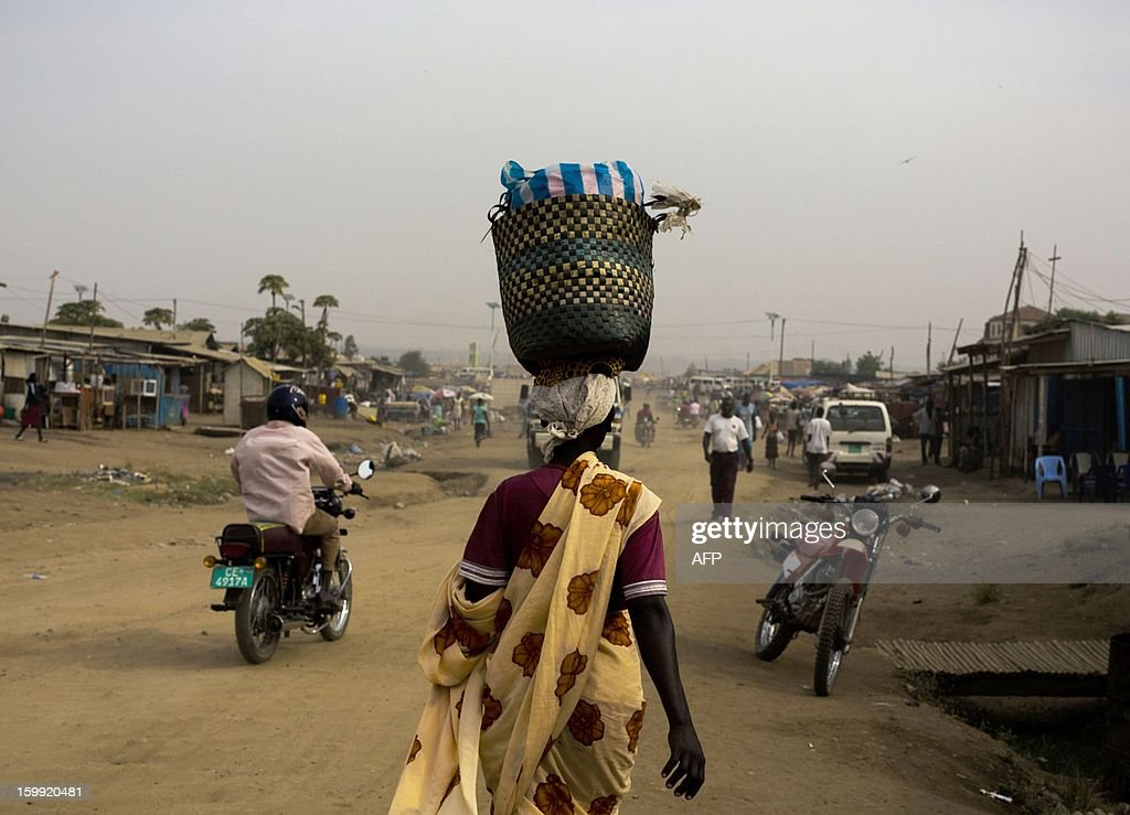 A South Sudanese woman carryies a basket on her head as she walks through Gudele market in Juba, South Sudan on January 23, 2012. Gudele was the scene of last year's (December 18) murder of writer Isaiah Abraham, an outspoken critic of the government whose death has raised concerns over press freedom in the fledgling nation, according to US embassy officials. Relatives say Diing Chan Awuol, who wrote under the pen name of Isaiah Abraham, was shot dead earlier this month for outspoken comments that included calling for an improvement in relations with former enemies in Khartoum. AFP PHOTO/ Camille Lepage