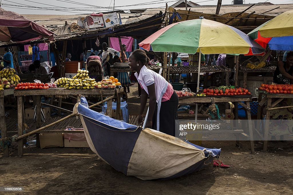 A South Sudanese woman picks up her parasol felled by the wind next to her fruit and vegetables stand at Gudele market in Juba, South Sudan January 23, 2012. Gudele was the scene of last year's (December 18) murder of writer Isaiah Abraham, an outspoken critic of the government whose death has raised concerns over press freedom in the fledgling nation, according to US embassy officials. Relatives say Diing Chan Awuol, who wrote under the pen name of Isaiah Abraham, was shot dead earlier this month for outspoken comments that included calling for an improvement in relations with former enemies in Khartoum. AFP PHOTO/ Camille Lepage