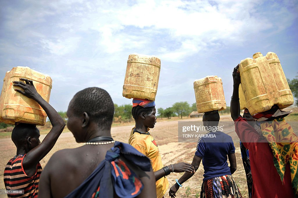 South Sudanese women carry jerry-cans filled with water on their heads on April 2, 2009, at Terekeka, 82 km north of Juba, an area where the population is exposed to malaria, a vector-borne, infectious parasitic disease that is a leading cause of death of infants and children in Africa. Some 4-10 billion US dollars is still needed to ensure the achievement of the universal coverage of more than 6 million people by 2010 according to the Global Fund to Fight AIDS, Tuberculosis and Malaria who sponsor ongoing intervention programmes in south Sudan. UN Secretary General Ban Ki-moon said on March 31, in a video message played at the start of a two-day meeting in Spain of key donors to the Global Fund that malaria cost Africa 12 billion dollars a year, but just 3.4 billion dollars is needed annually for prevention and treatment. AFP PHOTO / Tony KARUMBA