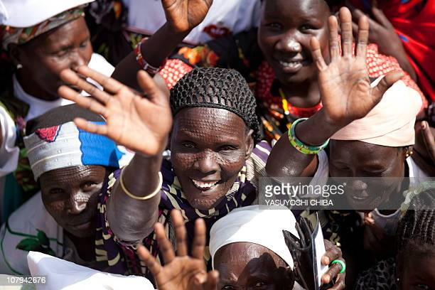 South Sudanese women from the Nuer tribe wave to photographers as they wait outside a polling station in the southern town of Bentiu capital of...
