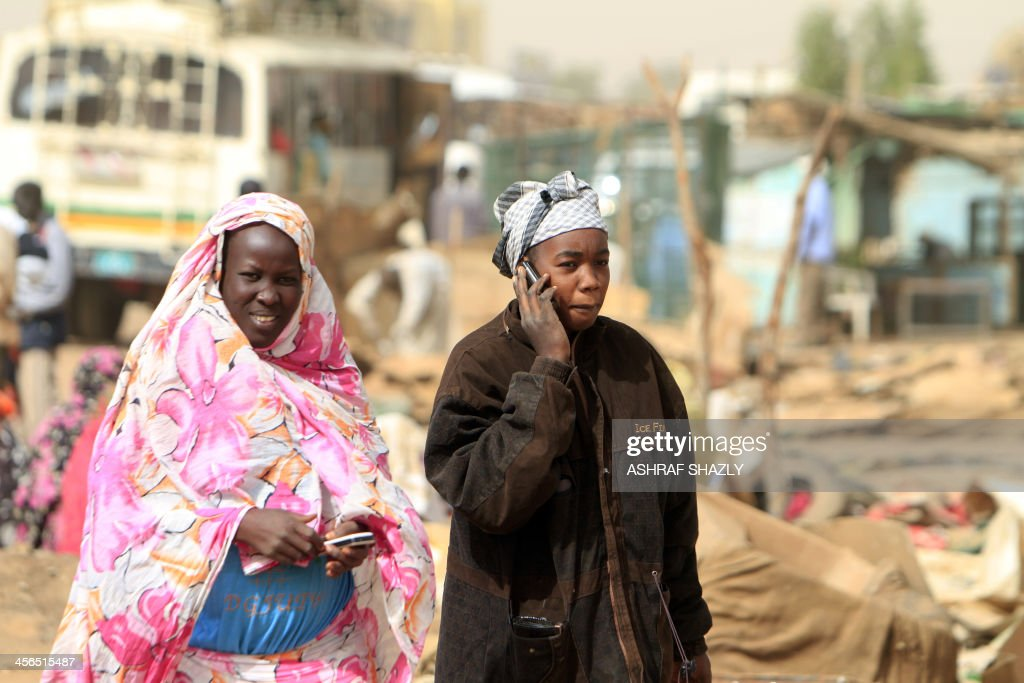 South Sudanese women use their phones ahead of their trip back to the South in Khartoum on December 14 2013 The group leaving for South Sudan's...