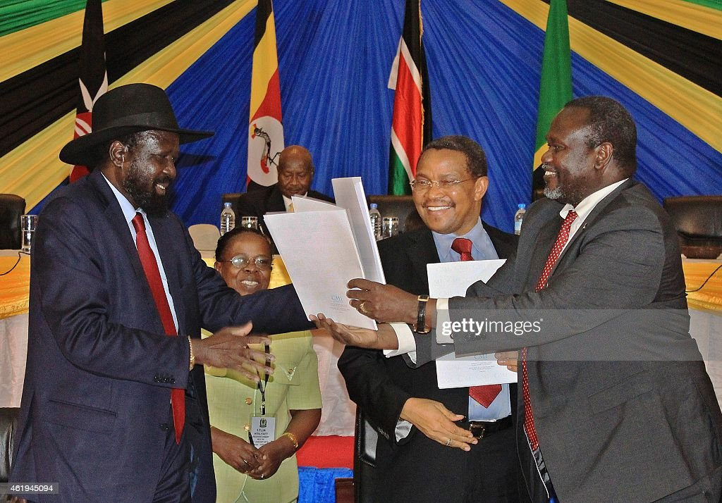 South Sudan's President Salva Kiir (L) exchanges signed documents with South Sudanese rebel leader <a gi-track='captionPersonalityLinkClicked' href=/galleries/search?phrase=Riek+Machar&family=editorial&specificpeople=579985 ng-click='$event.stopPropagation()'>Riek Machar</a> in northern Tanzania's town of Arusha on January 21, 2015, as Tanzania's President <a gi-track='captionPersonalityLinkClicked' href=/galleries/search?phrase=Jakaya+Kikwete&family=editorial&specificpeople=547422 ng-click='$event.stopPropagation()'>Jakaya Kikwete</a> (C) looks on. The leaders of South Sudan's warring factions on on January 21 agreed to a political deal designed to boost efforts to end their year-old civil war, diplomats said. President Salva Kiir and rebel leader <a gi-track='captionPersonalityLinkClicked' href=/galleries/search?phrase=Riek+Machar&family=editorial&specificpeople=579985 ng-click='$event.stopPropagation()'>Riek Machar</a> signed a pact in the northern Tanzanian city of Arusha to bring together the rival camps of the ruling Sudan People's Liberation Movement (SPLM).