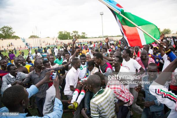 South Sudan's Wurube Robert is carried by fans as they celebrate defeating Somalia during the first round African Nations Championship qualifying...