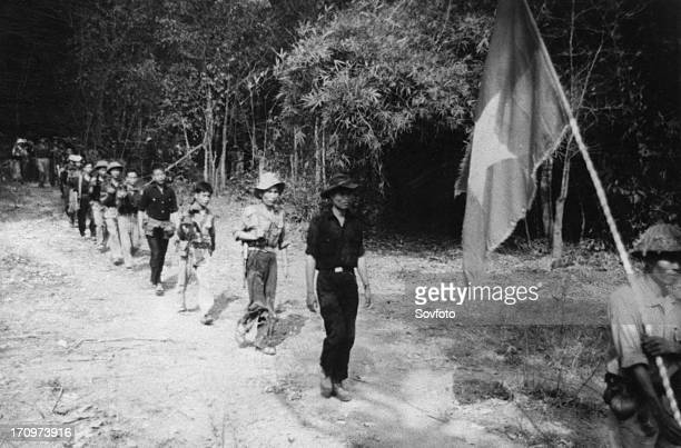 South vietnamese guerrillas file through the jungle along the ho chi minh trail the flag with a yellow star on a red and blue background is always...