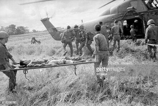 South Vietnamese paratroops injured in action are stretchered onto an evacuation helicopter in the demilitarized zone on the border of North and...