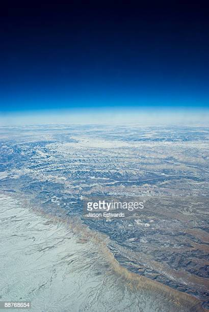 A high altitude view of rugged desert mountain ranges covered in snow.