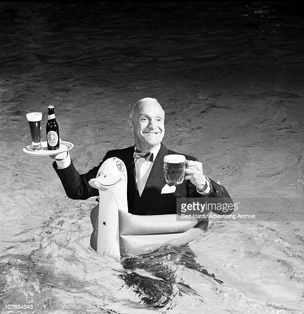 SouthAfrican born comedian 'Professor' Stanley Unwin standing with the aid of an inflatable duck in the swimming pool at the Dolphin Square...