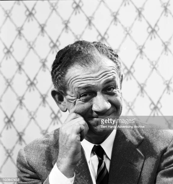 SouthAfrican comic actor Sid James pinching his cheek Ealing London 30th July 1960
