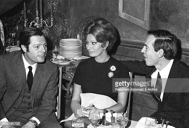 SouthAfrican surgeon Christiaan Barnard talking to Italian actors Marcello Mastroianni and Sophia Loren during a party in a villa Marino 31st January...