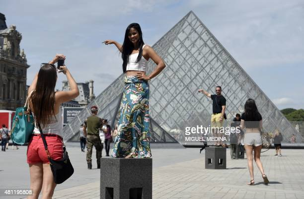 Southamerican tourists take pictures in front of the Louvre Pyramid in Paris on July 18 2015 in Paris AFP PHOTO / MIGUEL MEDINA