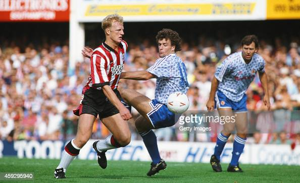 Southampton centre forward Iain Dowie beats Mark Hughes to the ball as Bryan Robson looks on during a League Division One match between Southampton...