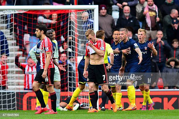 Southampton players argue with referee Mike Jones as James WardProwse of Southampton is shown a red card during the Barclays Premier League match...