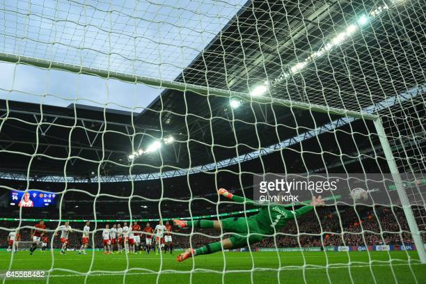 Southampton's English goalkeeper Fraser Forster dives but fails to reach the free kick from Manchester United's Swedish striker Zlatan Ibrahimovic...