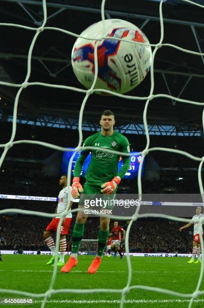 Southampton's English goalkeeper Fraser Forster looks back at the ball in his own net after Manchester United's English midfielder Jesse Lingard...