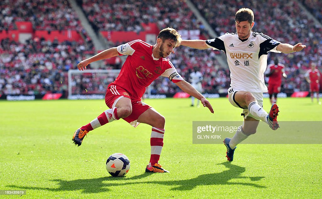 Southampton's English midfielder Adam Lallana (L) vies with Swansea City's Welsh defender Ben Davies (R) during the English Premier League football match between Southampton and Swansea City at St Mary's Stadium in Southampton on October 6, 2013. Southampton won the match 2-0.