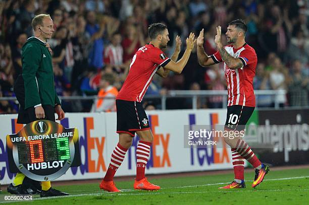 Southampton's English striker Charlie Austin highfives his replacement Southampton's English striker Jay Rodriguez as he leaves the pitch during the...