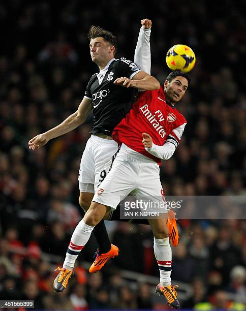 Southampton's English striker Jay Rodriguez challenges Arsenal's Spanish midfielder Mikel Arteta for a high ball during the English Premier League...
