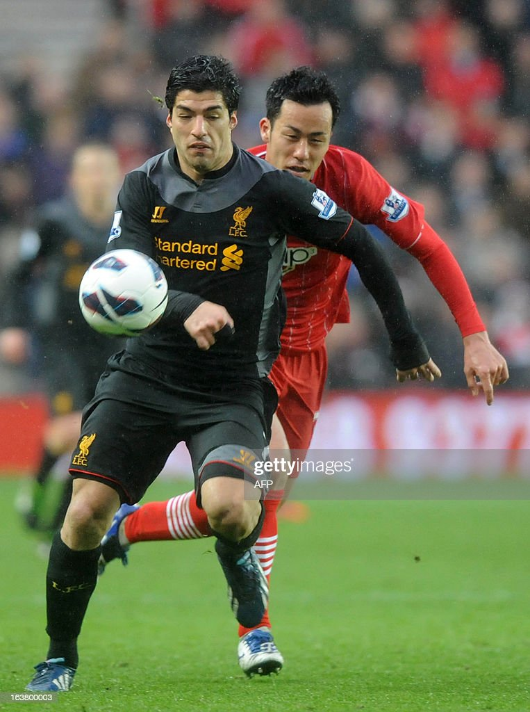 """Southampton's Japanese defender Maya Yoshida (R) vies with Liverpool's Uruguayan player Luis Suarez during the Barclays Premier League football match between Southampton and Liverpool at St Mary's Stadium in Southampton on March 16, 2013. Southampton won 3-1. AFP PHOTO/Olly Greenwood USE. No use with unauthorized audio, video, data, fixture lists, club/league logos or """"live"""" services. Online in-match use limited to 45 images, no video emulation. No use in betting, games or single club/league/player publications.7 2981656. Do not alter/modify photo."""