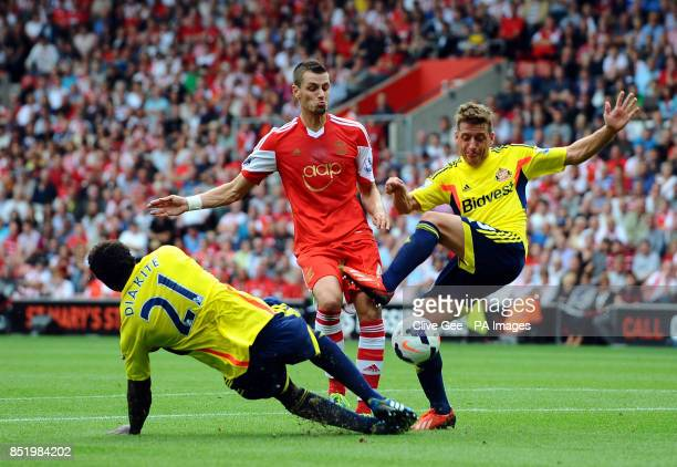 Southampton's Morgan Schneiderlin is challenged by Sunderland's Modibo Diakite and Emanuele Giaccherini during the Barclays Premier League match St...