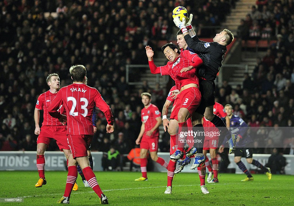 """Southampton's Polish goalkeeper Artur Boruc (R) claims the ball under pressure from Arsenal's French defender Laurent Koscielny (2nd R) during the English Premier League football match between Southampton and Arsenal at St Mary's Stadium in Southampton, southern England on January 1, 2013. The game finished 1-1. AFP PHOTO/GLYN KIRK USE. No use with unauthorized audio, video, data, fixture lists, club/league logos or """"live"""" services. Online in-match use limited to 45 images, no video emulation. No use in betting, games or single club/league/player publications."""