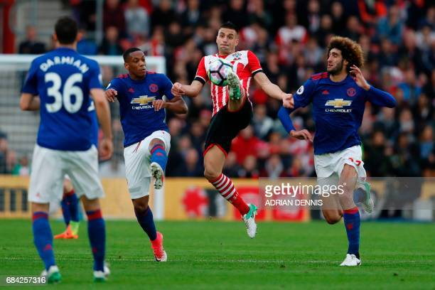 Southampton's Serbian midfielder Dusan Tadic leaps to pass the ball between Manchester United's Belgian midfielder Marouane Fellaini and Manchester...