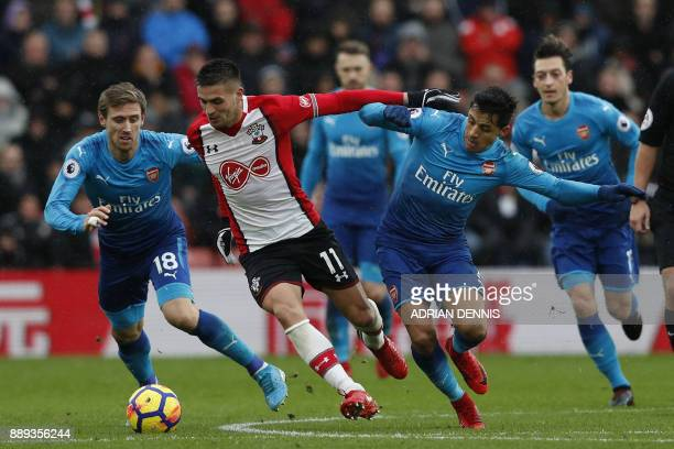 TOPSHOT Southampton's Serbian midfielder Dusan Tadic vies with Arsenal's Spanish defender Nacho Monreal and Arsenal's Chilean striker Alexis Sanchez...