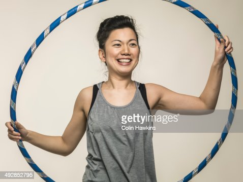 Southeast Asian female exercising with hoola-hoop