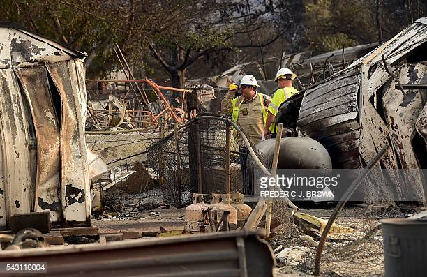 Southern California Edison workers from the Disaster Assesment Team inspect the electricity situation amid demolished South Lake homes in Lake...
