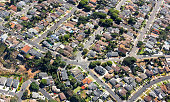 Multiple houses are seen from an aerial viewpoint over a residential neighborhood in southern California.